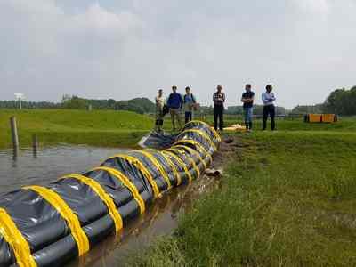 De tijdelijke waterkering over een hobbel. Een stapel stenen onder de Barrier moet een stoeprand voorstellen